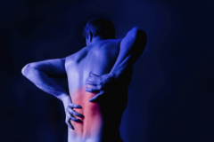A man holding his back in pain. Studio shot with red marking the area of pain.